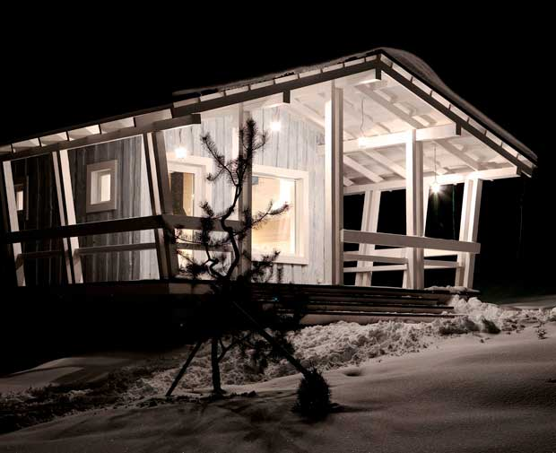 Una vista nocturna de la fachada de este hermosa cabaña.